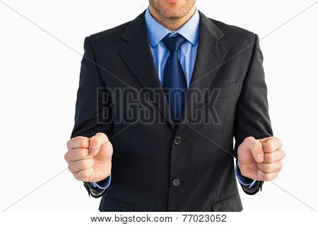 Businessman standing clenching his fists on white background