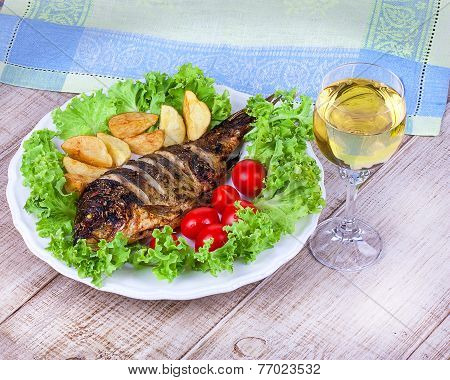 Whole grilled fish carp served with potatoes tomatoes cherry salad and lemon