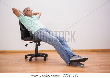 Mature man leaning back in swivel chair at home in the living room