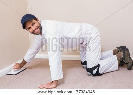 Handyman laying down a carpet in a new house