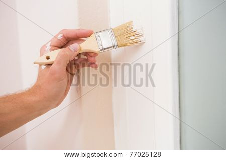 Painter painting the door white in a new house