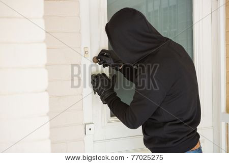 Burglar breaking open the door of someones home