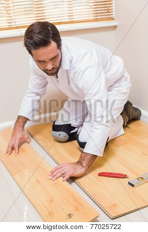 Carpenter putting down new wooden planks in a new house