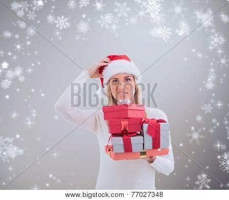 Confused blonde in santa hat holding gifts against grey vignette