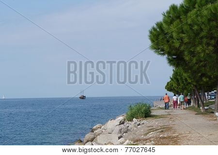 People walking on a promenade in Piran