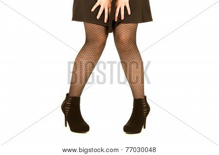 Womans Legs Wearing Black Dress And Fishnet Stockings