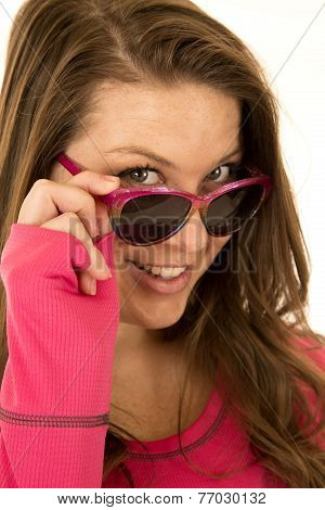 Young Brunette Woman Peering Over Her Sun Glasses Smiling