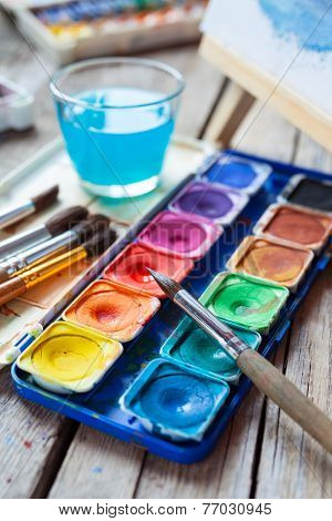 Set Of Watercolor Paints,  Art Brushes,  Glass Of Water And Easel With Painting On Wooden Background