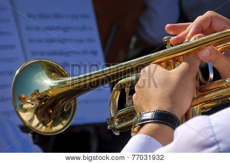 Musician playing trumpet in street orchestra