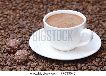 cup of coffee and candies on a coffee beans background