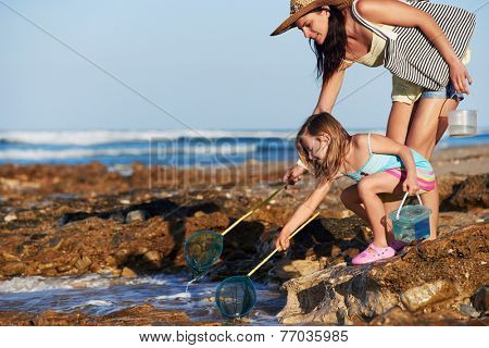 Mother and daughter spend the day fishing at the beach together having fun and bonding over some quality parent childhood time