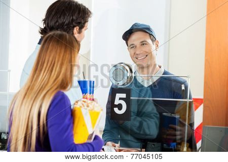 Mid adult couple holding snacks while buying movie tickets from seller at box office