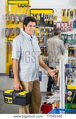 Portrait of confident young male customer buying hammer with man in background at hardware store