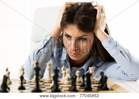 Young Worried Businesswoman In Front Of The Chessboard