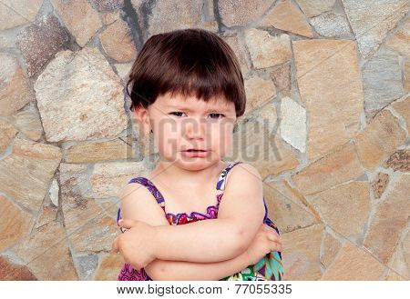 Sad baby girl with a stone wall of background