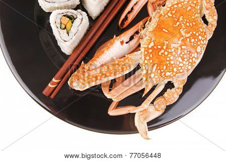 Roll with Cucumber , Cream Cheese with raw Tuna and Salmon inside. on black dish with boiled crab . Japanese traditional Cuisine
