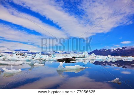 Cirrus clouds are beautifully reflected in the smooth water of the ocean lagoon. J�?�?�?�¶kuls�?�?�?�¡rl�?�?�?�³n Glacial Lagoon in Iceland