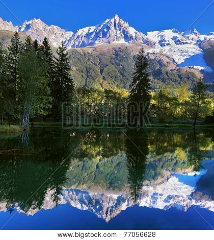 Snowy mountains and evergreen forests in the famous mountain resort of Chamonix. Gorgeous reflection in the smooth water of the lake in the park