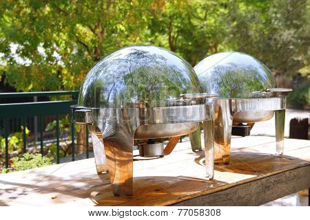two closed stainless steel cloche on wooden table on restaurant outside party