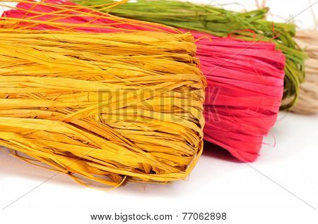 some skeins of natural raffia of different colors on a white background