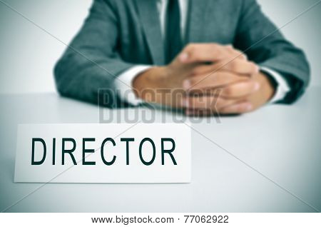 a man in suit sitting in a desk with a nameplate in front of him with the word director written in it