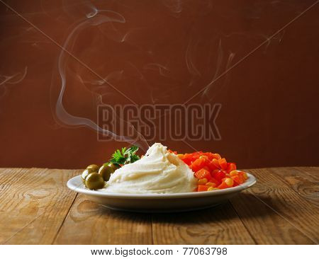 Delicious home cooked food with steam on table on brown background