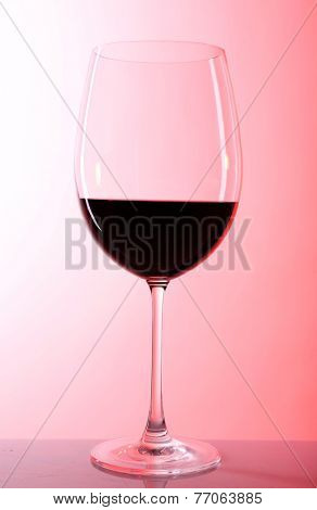 Red wine glass of wine on colorful background