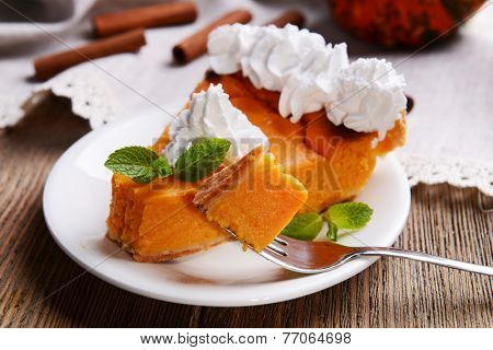 Piece of homemade pumpkin pie on plate on wooden background