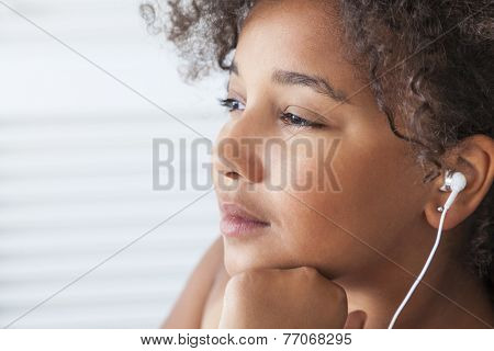 Young mixed race African American girl child listening to MP3 music player on white headphones or earphones