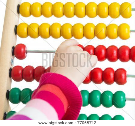 Child's hand counting on colorful abacus isolated