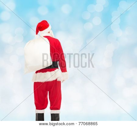 christmas, holidays and people concept - man in costume of santa claus with bag from back over blue lights background
