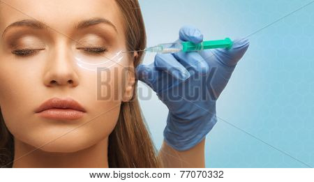 medicine, plastic surgery, beauty, health and people concept - close up of hand in medical glove with syringe making injection to beautiful woman face over blue background
