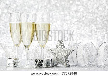 Champagne glasses and christmas decoration on silver bokeh background