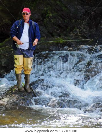Fly Fisherman at Base of Waterfall