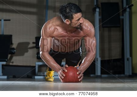 Attractive Male Athlete Performing Push-ups On Medicine Ball