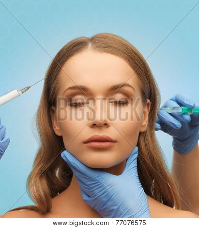 medicine, plastic surgery, beauty, health and people concept - hands in medical glove with syringe making injection to beautiful woman face over blue background