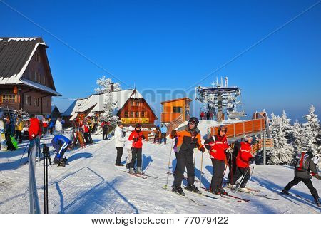 HIGH TATRAS, SLOVAKIA - JANUARY 01, 2010: Skiers in bright jackets are going on a ski trip.  Sunny morning in January at the ski resort