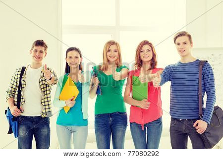 education and school concept - group of smiling students with bags and folders at school showing thumbs up
