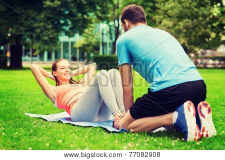 fitness, sport, training, teamwork and lifestyle concept - smiling woman with personal trainer doing exercises on mat outdoors