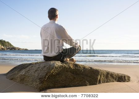 Businessman Meditating On A Beach