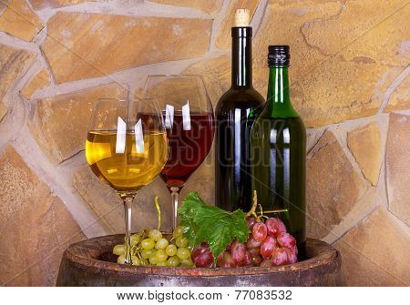 Glasses and bottles of wine on old barrel with iron rings
