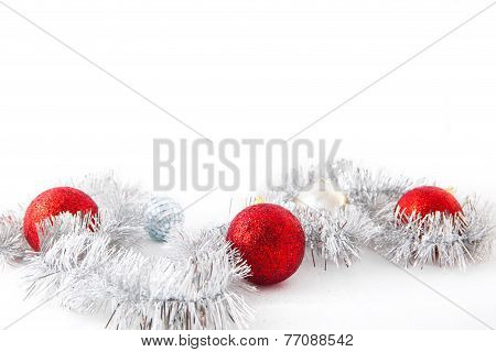 Red balls on silver tinsel. Isolated over white.