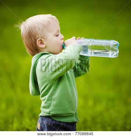 little boy drinks mineral water