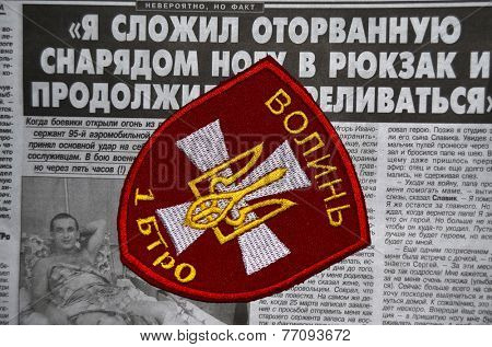 Kiev,Ukraine.Oct 16.Illustrative editorial.Pro-Ukranian nationalist formations Volyn chevrone .Newspaper with heroic story of soldier as background.At October 16,2014 in Kiev, Ukraine