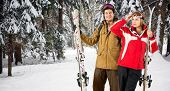 foto of blanket snow  - Two skiers holding their skies in the deep powder snow in a forest during their winter holiday - JPG