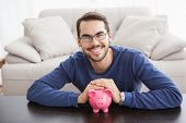 picture of piggy  - Smiling young man with piggy bank at home in the living room - JPG