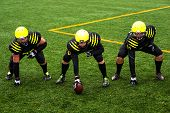 stock photo of football helmet  - Men in green sportswear and helmet playing american football on the sports ground - JPG