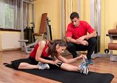 stock photo of supervision  - Beautiful young girl doing stretching exercises in the gym under supervision of her coach - JPG