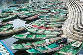 pic of conic  - Vietnamese woman with conical hat sitting in a traditional boat on the river - JPG