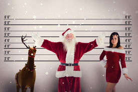 stock photo of mug shot  - Jolly Santa opens his arms to camera against mug shot background - JPG